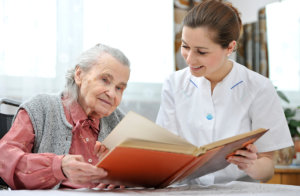 caregiver and old woman reading book